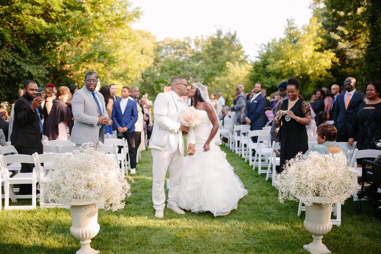 Bride and groom kiss at outdoor wedding ceremony at graydon hall manor